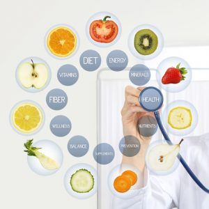 smiling nutritionist doctor with stethoscope pointing symbols fruits icons and medical texts isolated on white background, healthy food supplements diet plan concept (smiling nutritionist doctor with stethoscope pointing symbols fruits icons and medic