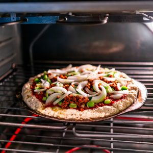 Inside oven with rack and homemade pizza cooking baking with tomato sauce, toppings green bell peppers onions chopped with ground vegan beef crumbles